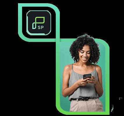 Mulher, de pé, segurando um celular com as duas mãos, sorrindo e com camiseta de alça cinza e calça bege.